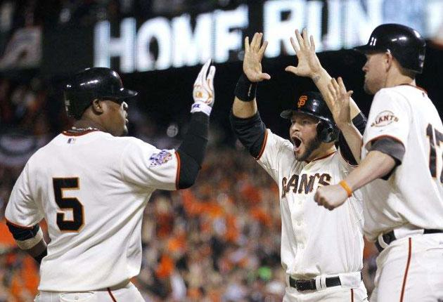 San Francisco Giants' Juan Uribe, left, celebrates his three run homer with teammates Cody Ross and Aubrey Huff