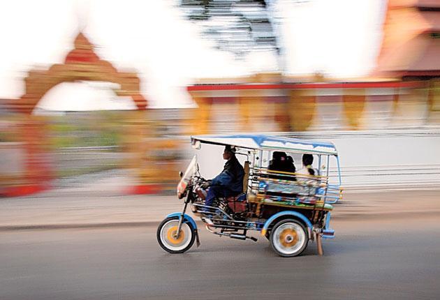 Wheel thing: A tuk tuk races through Vientiane, the capital of Laos