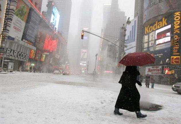 A pedestrian walks across Times Square during a snow storm