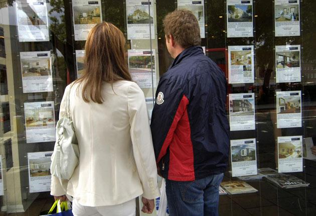 People outside an estate agent's window in London