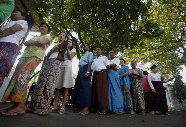 Under tight security, Burmese voters wait to cast their ballots yesterday