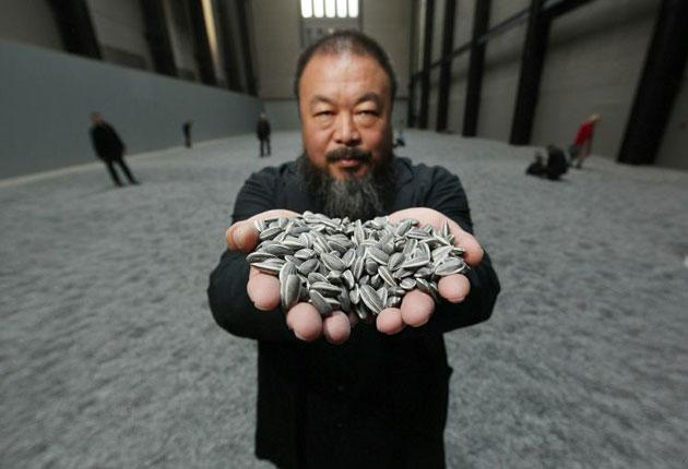 Ai Wei Wei with his installation, Sunflower Seeds, currently showing at Tate Modern