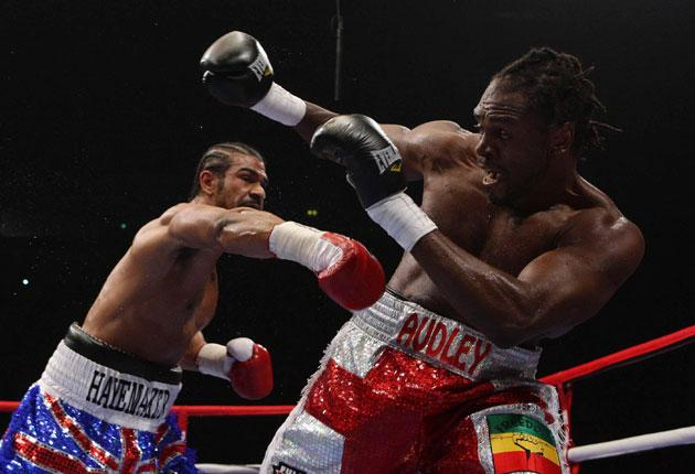 David Haye (left) unleashes a rapid right hand as a bewildered Audley Harrison takes cover in Manchester