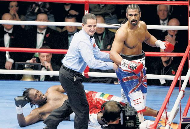 Evening over: Referee Luis Pabon ushers David Haye to his corner after he floors Audley Harrison