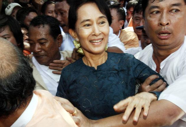 Aung San Suu Kyi is protected by bodyguards as she makes her way through thousands of cheering supporters into her party headquarters