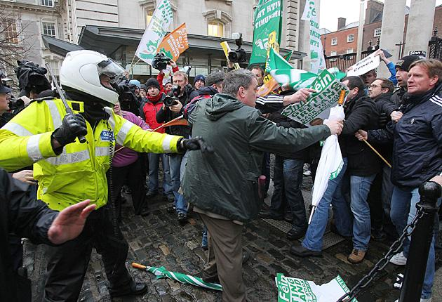 Sinn Fein protestors including TD Aengus O' Snodaigh (centre) tussle with Gardai at the gates of Government Buildings in Dublin
