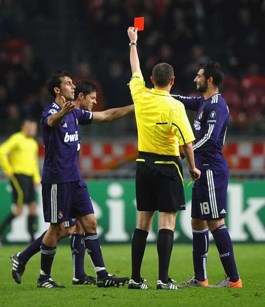 Referee Craig Thomson of Scotland sends off Xabi Alonso of Real Madrid for time wasting