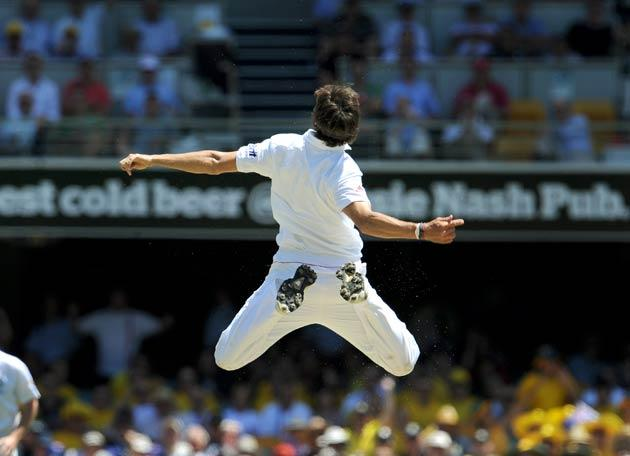 England bowler Steve Finn leaps in the air after dismissing Australian batsman Simon Katich
