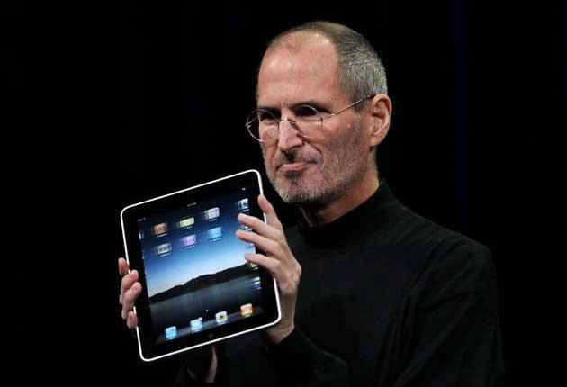 Steve Jobs holds an iPad, one of 4.2 million sold