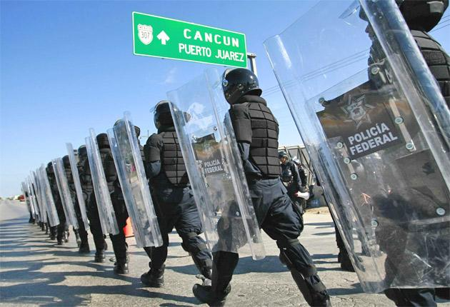 Riot police stand ready while protesters march outside the UN conference