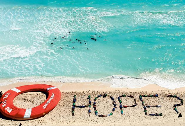 Greenpeace activists add a question mark to the word 'hope', giving a cautious welcome to the Cancun deal