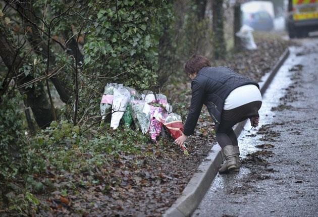 A woman places flowers where Joanna Yeates's frozen body was found