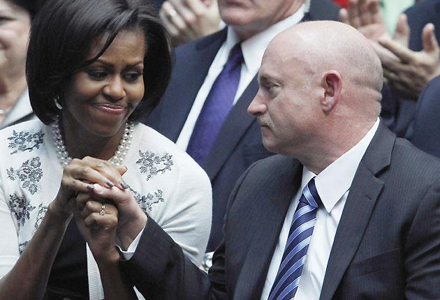 The US first lady Michelle Obama holds the hand of Congresswoman Gabrielle Gifford's husband, NASA shuttle commander Mark Kelly, as they listen to President Barack Obama speak at the University of Arizona