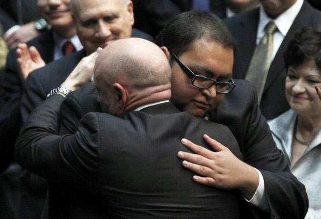 Daniel Hernandez hugs Mrs Giffords' husband, astronaut Mark Kelly, during the memorial event in Tucson
