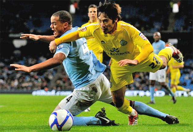 Yuki Abe of Leicester City (right) tangles with Vincent Kompany of Manchester City at Eastlands last night