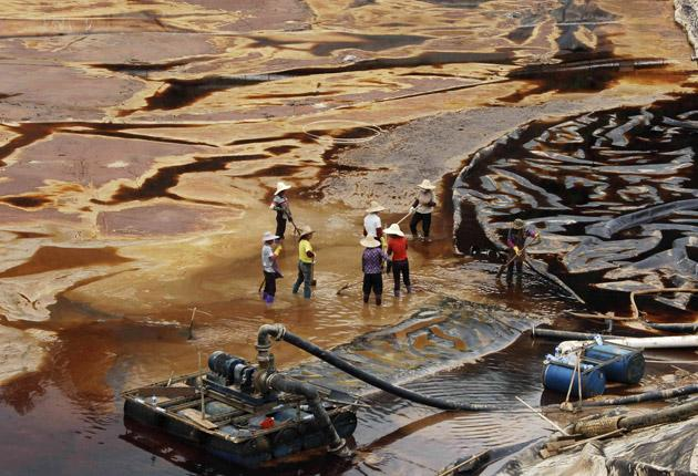 Workers drain away polluted water near the Zijin copper mine in Shanghang