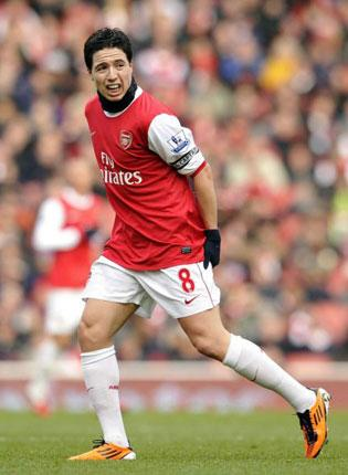 Arsenal's Samir Nasri grabs his leg as he pulls up with a hamstring injury yesterday which is likely to keep him out of action for at least three weeks