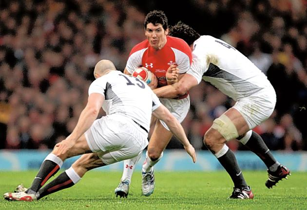 James Hook, of Wales, is tackled by Mike Tindall (left) and Louis Deacon (right) at the Millennium Stadium last night