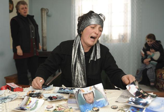 Dodo Kharazishvili, mother of late Georgian olympic luger Nodar Kumaritashvili, cries while looking at photos of her son at their home
