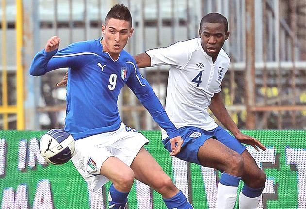 Italy's Federico Macheda (left) holds off England's Fabrice Muamba in Empoli yesterday