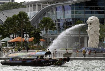 A river taxi sails past the Merlion on the waterfront of the financial district in Singapore.