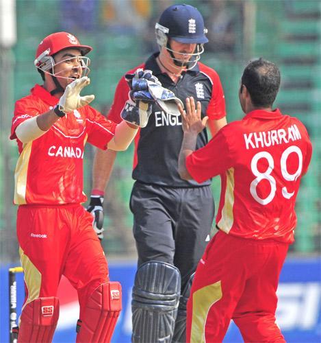 Canada's Ashish Bagai celebrates the dismissal of Kevin Pietersen (centre) with Khurram Chohan