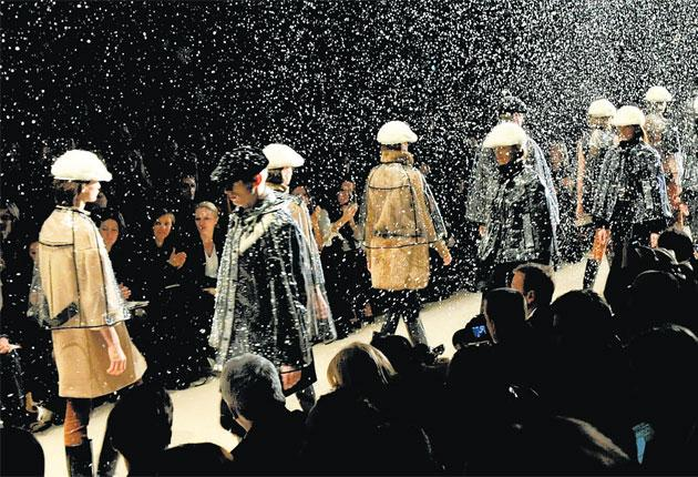 Models in clear vinyl ponchos brave a fake snowstorm to show off Christopher Bailey's new designs for Burberry