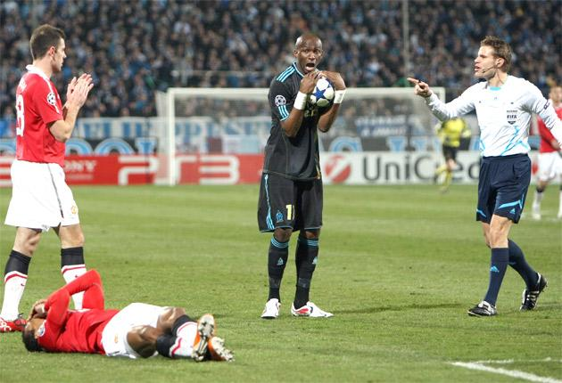 Referee Felix Brych lectures Marseille's Stephane Mbia for a foul on United's Portuguese winger Nani