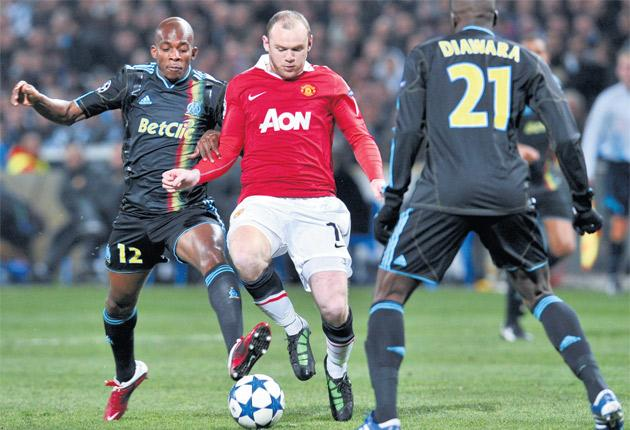 Wayne Rooney is crowded out by Stephane M'Bia (left) and Souleymane Diawara (right) during Manchester United's draw against Marseilles last night