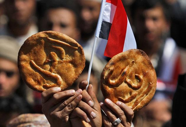 Protesters in Yemen yesterday holding bread with 'Leave' written on it