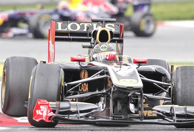 Nick Heidfeld's Lotus Renault is followed by Mark Webber in his Red Bull during testing at the Circuit de Catalunya yesterday