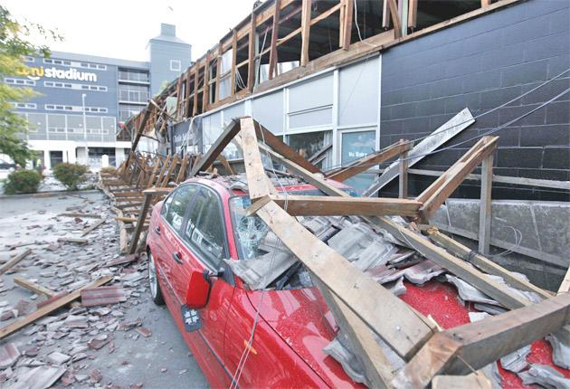 A car lies under rubble outside the AMI Stadium in Christchurch after the 22 February quake