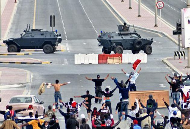 Protesters confront military vehicles near Pearl Square in Manama