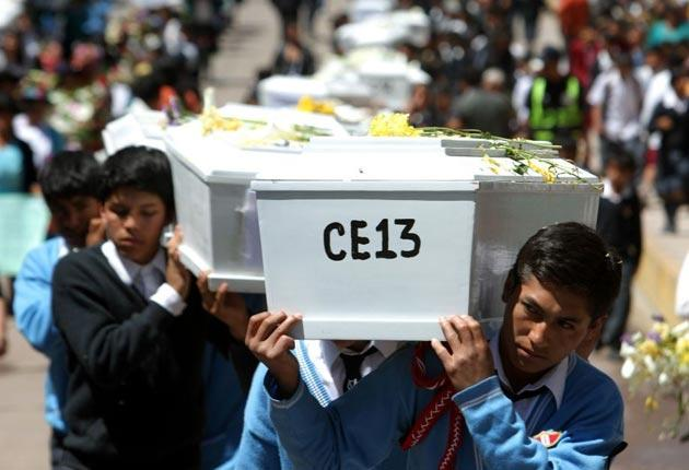 Students carries coffins containing remains of people killed in a 1984 massacre