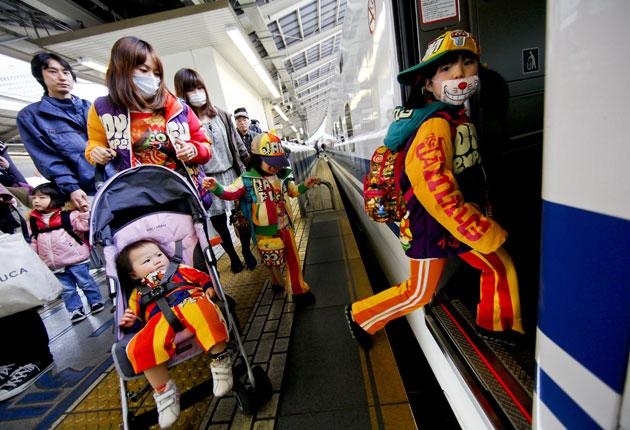 A young family boards the bullet train in Tokyo last week - though many Japanese are staying in the city despite fears of radiation