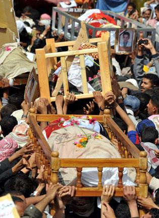 Mourners carry the coffins of some of the 50 anti-government protesters killed in the Yemeni capital, Sana'a