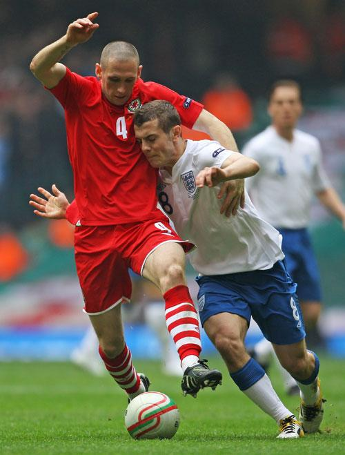 England's Jack Wilshere (right) is challenged by Andrew Crofts