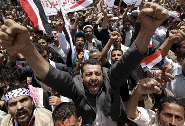 Anti-government protesters shout slogans during a rally to demand the resignation of Yemen's president