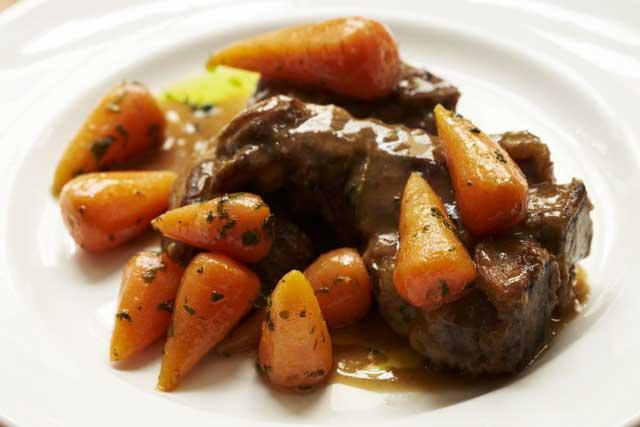 Mutton chops cooked in beer with spring carrots