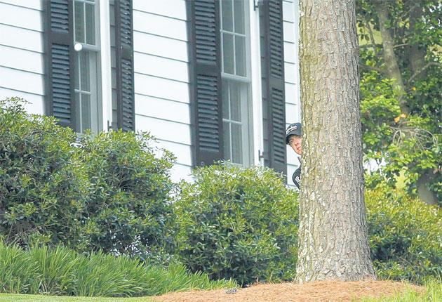 Rory McIlroy chips out from next to the cabins along the 10th fairway during his horror hole at the Masters on Sunday