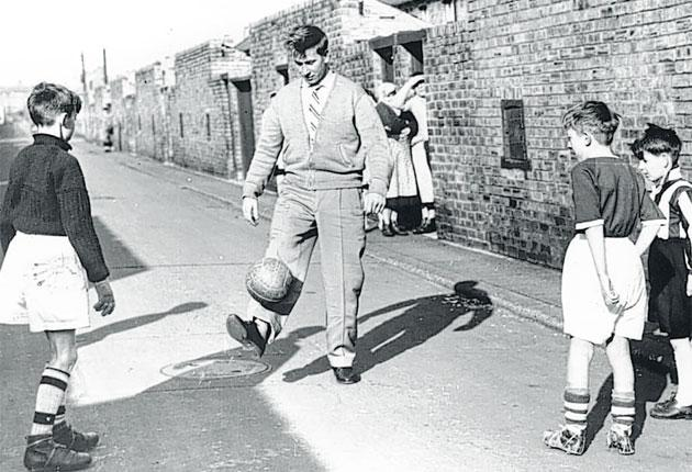 Bobby Charlton, then recovering from his injuries sustained in the Munich disaster, joins young fans for a kickabout