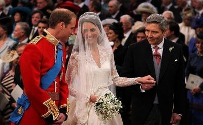 Britain's Prince William (L) looks at his bride Kate Middleton (C), as she holds her father Michael Middleton's hand.