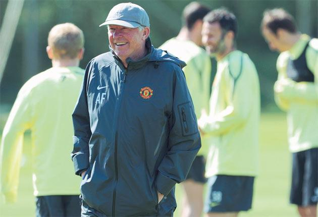 Sir Alex Ferguson enjoys a light-hearted moment during a United training session at Carrington