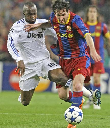 Real Madrid's Lassana Diarra attempts to halt the progress of Barcelona's Lionel Messi at the Nou Camp last night