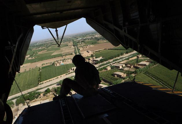 A member of the US Marine helicopter CH 53 crew sits at the back door as it flies over Marjah district in Helmand Province