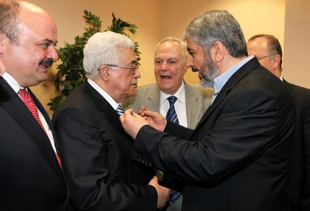 President Mahmoud Abbas, the Fatah leader, shakes hands with Hamas leader Khaled Meshaal