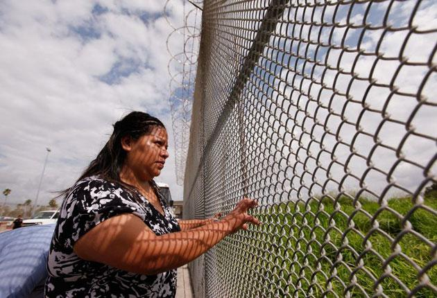 : A Mexican woman looking through the border fence before being deported from Brownsville