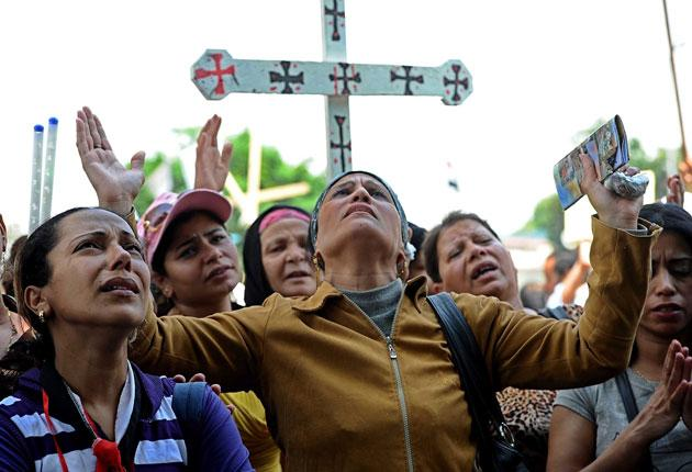 Egyptian Coptic Christians hold crosses and pray during a protest outside the Media Ministry in Cairo. They have come under attack but are supported by the Coptic community