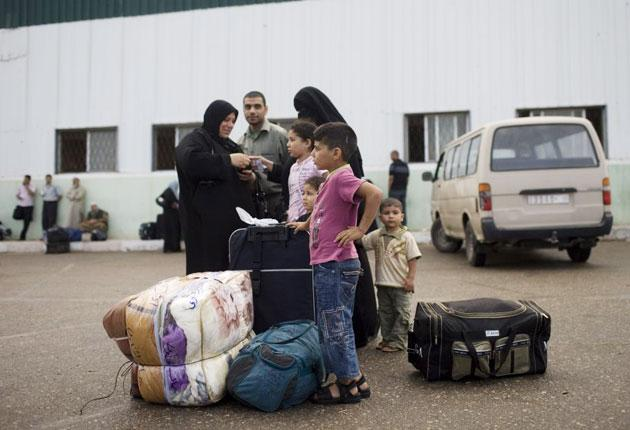 A Palestinian family wait before crossing into Egypt through the Rafah border crossing