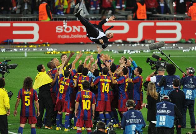 The manager Pep Guardiola is thrown into the air as Barcelona players celebrate